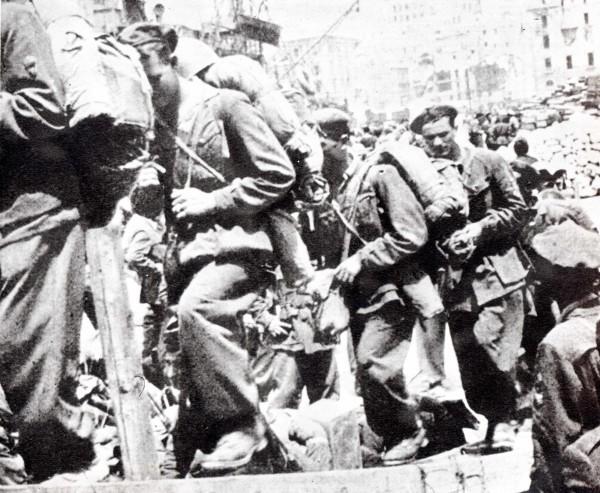 """Uomini della divisione paracadutisti """"Nembo"""" s'imbarcano in un porto della Sardegna per essere trasportati in continente. Anch'essi saranno poi aggregati ai Gruppi di combattimento."""
